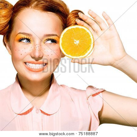Beauty Model Girl with Juicy Oranges. Beautiful Joyful teen girl with freckles, funny red hairstyle and yellow makeup . Professional make up. Orange Slices. Isolated on a white background