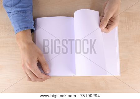 Men reading empty open book on wooden table background