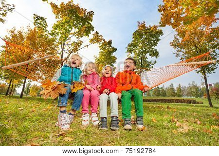 Group of happy children sitting on hammock in park