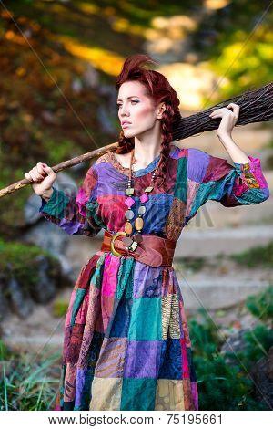 Fashionable girl holding broom