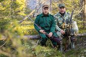 stock photo of hunters  - Two older hunters rest sitting on a log - JPG
