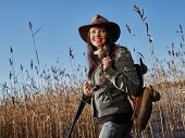 picture of shotgun  - Waterfowl hunting smiling female hunter carry a shotgun and a decoys reeds and blue sky on background - JPG
