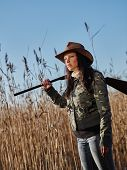 stock photo of shotgun  - Waterfowl hunting female hunter carry a shotgun reeds and blue sky on background - JPG