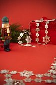 foto of nutcracker  - A Nutcracker stand guard by a Christmas present.