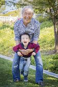 foto of grandpa  - Happy Chinese Grandpa Having Fun with His Mixed Race Grandson Outside - JPG