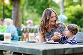 picture of little young child children girl toddler  - Young mother relaxing together with her little child adorable toddler girl in summer outdoors cafe drinking coffee and eating muffin or cupcke - JPG