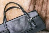 foto of mink  - A black leather bag of warm blond sheepskin blue fox and red sable mink furs - JPG