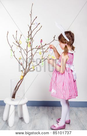 Girl holds basket with Easter eggs and decorates magnolia branch