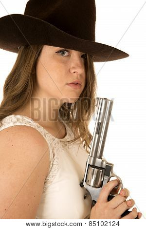 Cowgirl Staring At Camera Holding A Large Pistol