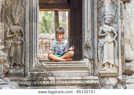 young happy child boy tourist meditating in angkor wat, cambodia