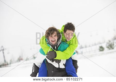 Young male friends enjoying piggyback ride in snow