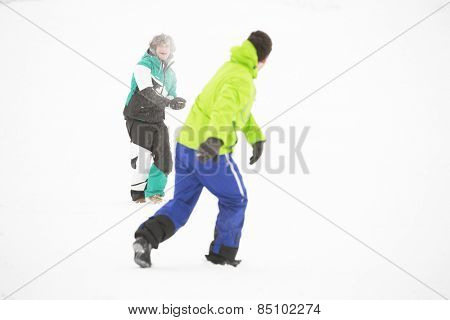 Full length of friends having snowball fight