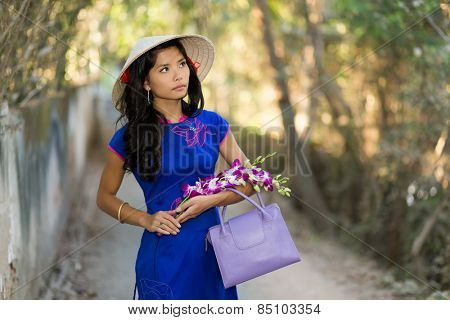 pretty young Vietnamese woman in a stylish blue outfit carrying flowers as she walks through a tree-lined avenue in the park