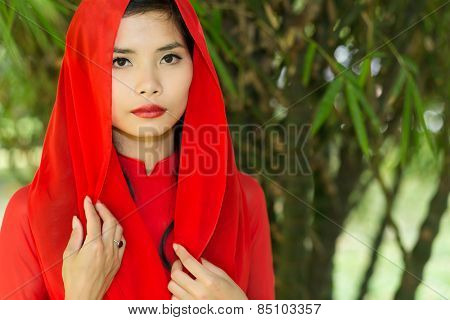 Pretty Vietnamese woman in a red head scarf standing with her hands to her chest looking at the camera with a serious expression