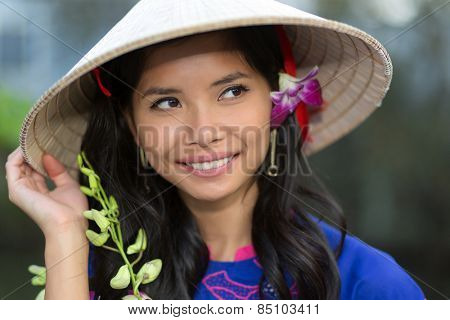 Pretty Vietnamese woman wearing a traditional conical hat with a flower in her hair smiling happily as she looks up into the air