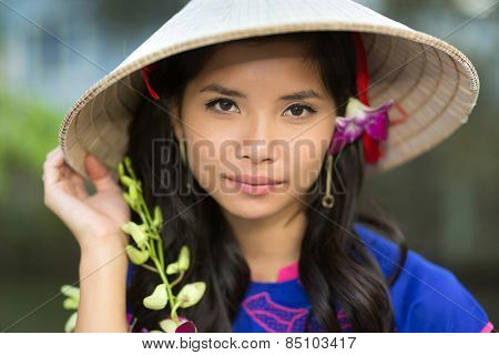 Attractive serious young Vietnamese woman in a conical straw hat with a fresh flower in her hair looking at the camera with her hand to the brim
