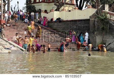 KOLKATA, INDIA - FEB 14: Hindu people bathing in the ghat near the Dakshineswar Kali Temple on February 14, 2014. At present time this river is being polluted tremendously.