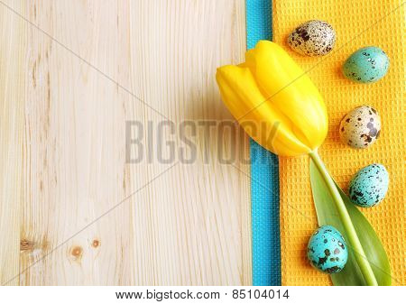 Yellow tulip, colorful eggs and napkin on plate, on wooden background