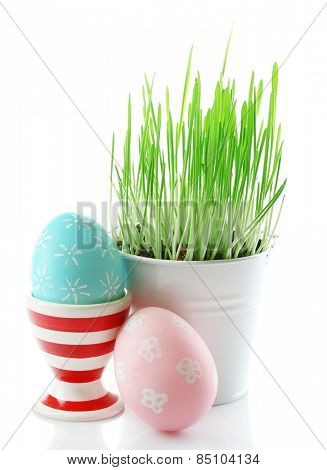 Fresh green grass in small metal bucket and Easter egg in stand, isolated on white