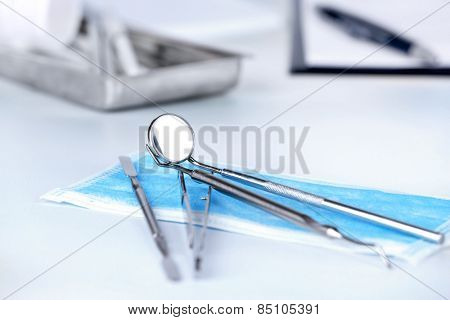 Dentist tools with medical mask on table close up