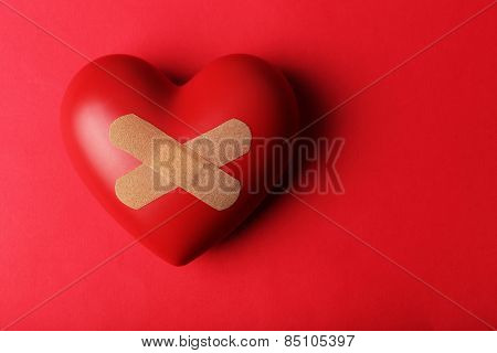 Heart with plaster on colorful background