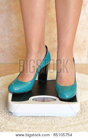 Woman's feet in high heels on bathroom scale