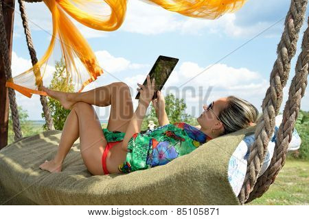 young woman relaxing in hammock with tablet
