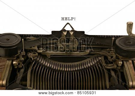 An old fashioned typewriter with the word HELP! Closeup of the antique machines ribbon and carriage Wit warm vintage tones.