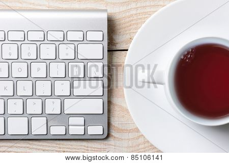 Closeup of a computer keyboard and cup of hot coffee on a white rustic table. High angle shot in horizontal format.
