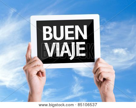 Tablet pc with text Have a Good Trip (in Spanish) with sky background