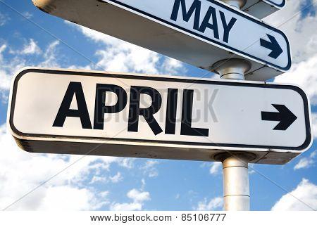 April direction sign on sky background