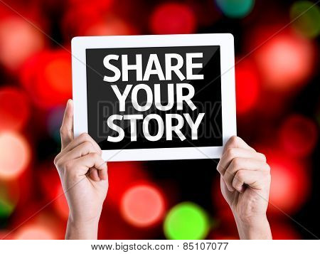 Tablet pc with text Share Your Story with bokeh background