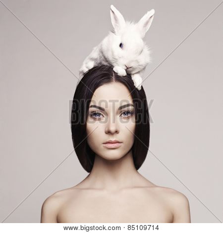 Studio fashion portrait of beautiful lady with white rabbit