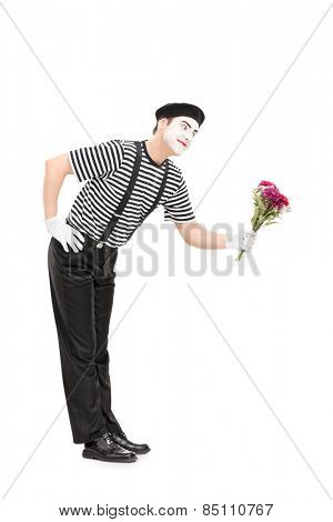 Full length portrait of a mime artist giving flowers to someone isolated on white background