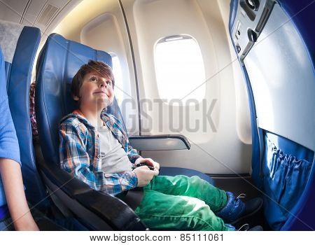 Happy little boy in airplane seat sit by window