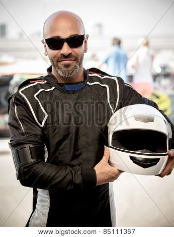 Race driver portrait, handsome man wearing sportive outfit and stylish sunglasses, holding helmet, happy winner of a race, active lifestyle concept