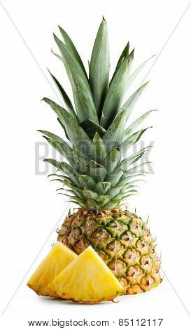 Half pineapple with leaves and cut pieces