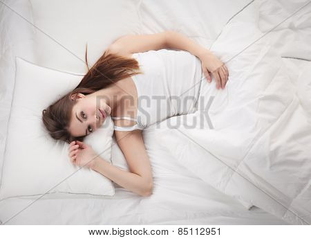 Beautiful girl lying in bedroom at early morning .