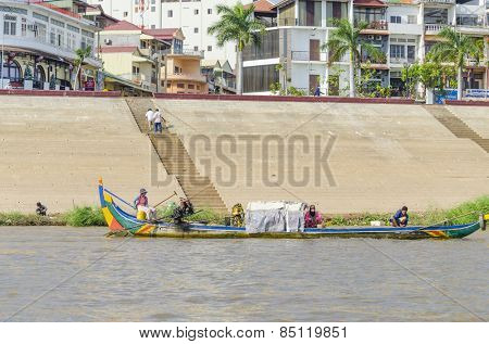 PHNOM PENH, CAMBODIA, JANUARY 2, 2013: Local people travel on fishing boat on Mekong river along the Sisowath Quay