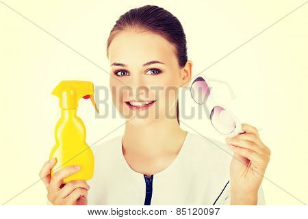 Woman doctor or nurse showing sunscreen and sunglasses.