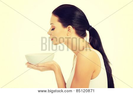 Beautiful caucasian woman smells her hot soup in bowl.