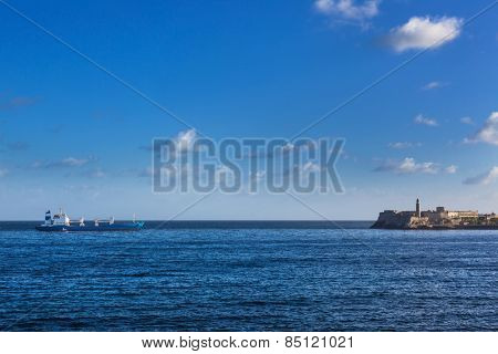 cargo ship and old fortress with lighthouse