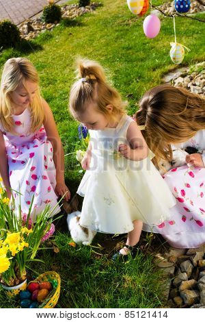 Children on an Easter Egg hunt on a meadow in spring, in the foreground a living Easter bunny is waiting