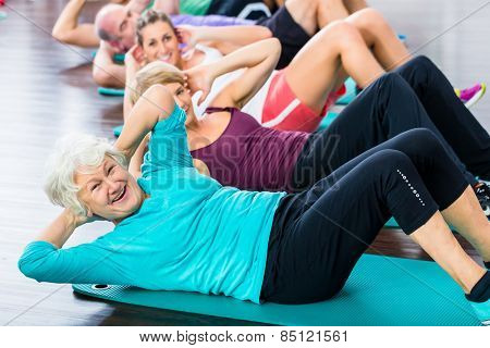 Group of senior people and young woman and men in fitness gym doing sit-ups on the floor