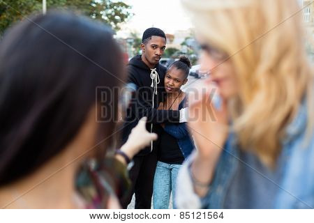 Racism - black couple being bullied, people pointing with finger on them