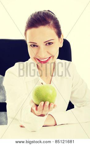 Happy businesswoman eating green apple.