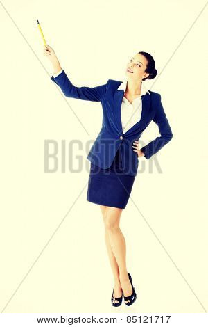 Happy attractive businesswoman pointing with pencil.