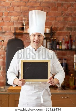 cooking and people concept - happy male chef cook with black blank menu chalk board in kitchen in restaurant kitchen