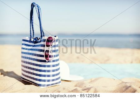 hats and summer concept - white straw hat, sunglasses and bag lying in the sand on the beach