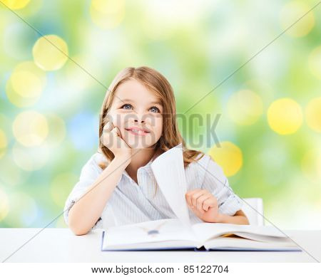 education, people, children and school concept - little student girl sitting at table with book over green lights background